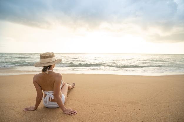 Lato posteriore della donna in bikini che si siede sulla spiaggia di sabbia rilassante per prendere il sole.