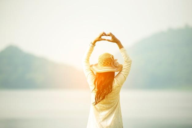 Lato posteriore della donna che si sente fresca libertà energia positiva in piedi campo di erba prato fiorito luce solare
