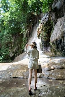 Lato posteriore della donna con cascata nella foresta pluviale tropicale con roccia saiyok noi cascata