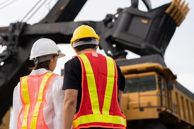 Lato posteriore dei lavoratori nelle miniere di lignite o carbone con il camion che trasporta carbone.