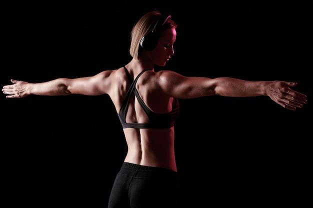 Dietro di una sportiva con un corpo muscoloso che si allunga dopo l'allenamento, la ragazza magra ascolta musica durante l'allenamento