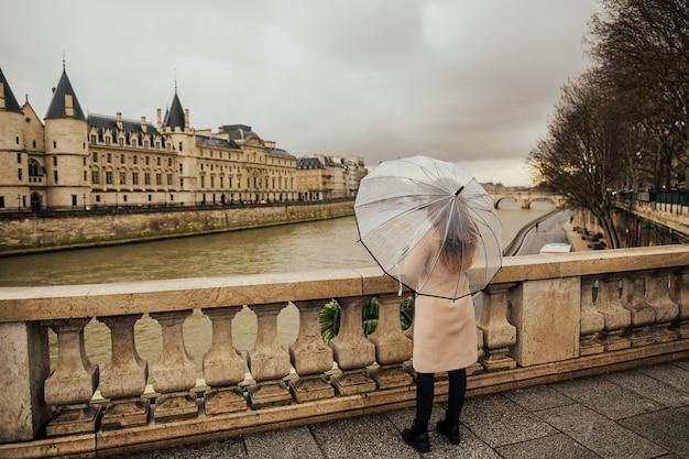 Retro della ragazza del viaggiatore che cammina a parigi sotto la pioggia e tiene in mano l'ombrello trasparente.