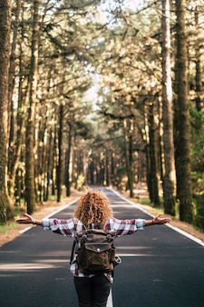 Vista posteriore della donna avventuriera che cammina sulla strada in mezzo alla foresta
