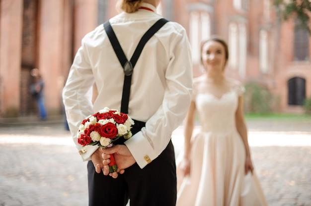 Vista posteriore di uno sposo in possesso di un bouquet da sposa di rose per la sua sposa felice