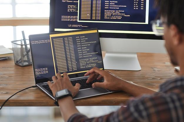 Vista posteriore a sviluppatore it afro-americano che digita sulla tastiera con codice di programmazione nero e arancione sullo schermo del computer e laptop, copia dello spazio