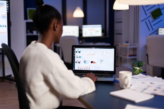 Vista posteriore di una donna d'affari africana che analizza le statistiche finanziarie lavorando a tarda notte