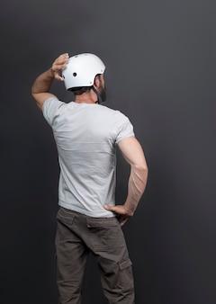 Vista posteriore dell'uomo barbuto bello americano in un casco da bicicletta. uomo russo dopo un intenso allenamento in bicicletta. persona attiva che guarda avanti e tiene la mano dietro la testa, in posa tenendo il casco