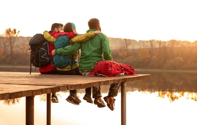 Vista posteriore di uomini anonimi e donna con zaini che abbracciano e seduti sul molo vicino al lago calmo al tramonto nella natura