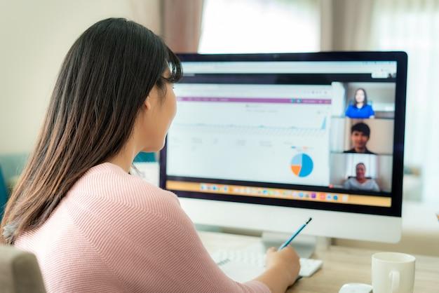 Punto di vista posteriore della donna asiatica di affari che parla con suoi colleghi del piano nella videoconferenza.
