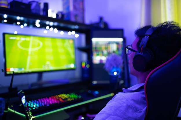 Vista posteriore dell'uomo asiatico gioca sul computer e lavora da casa