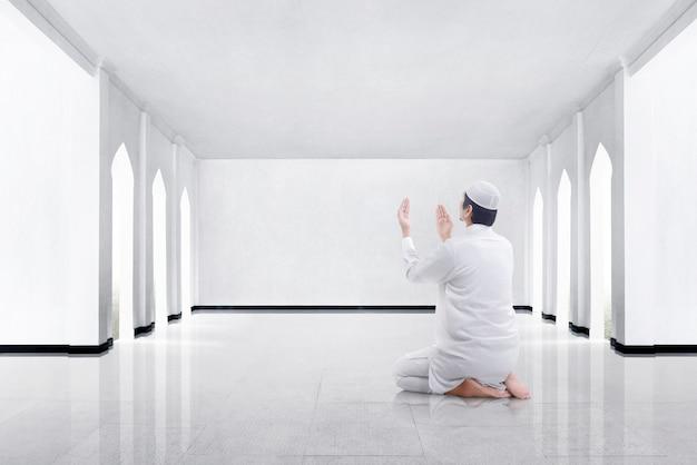 Punto di vista posteriore dell'uomo musulmano asiatico che si inginocchia e che prega dio