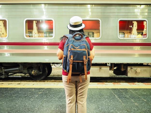 Vista posteriore del viaggiatore donna asiatica in attesa e guardando al treno alla piattaforma in thailandia.