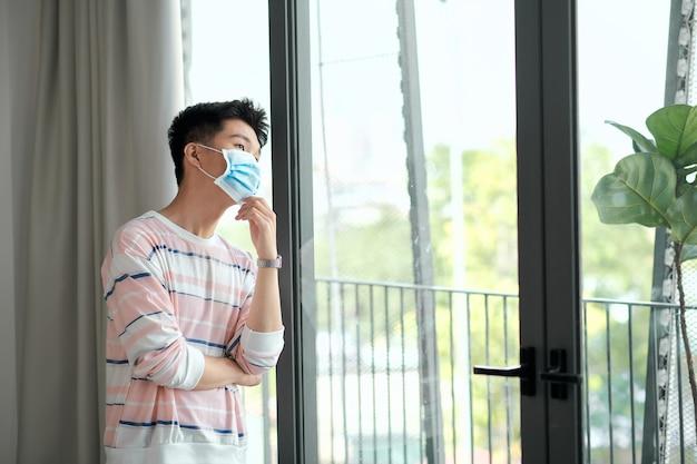 La vista posteriore del giovane asiatico che indossa la maschera facciale rimane in isolamento a casa per l'autoquarantena a causa dell'epidemia di covid19 - guarda fuori dalla finestra