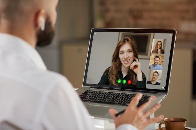 Vista posteriore di un impiegato maschio calvo in auricolari che sta gesticolando durante una videoconferenza a casa.