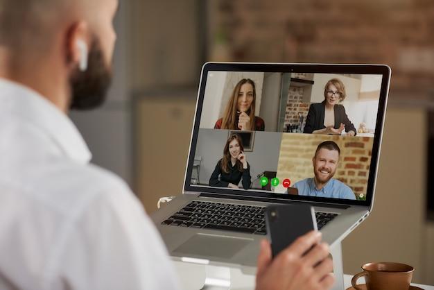 Vista posteriore di un impiegato maschio calvo in auricolari che tiene in mano un telefono durante una videoconferenza.
