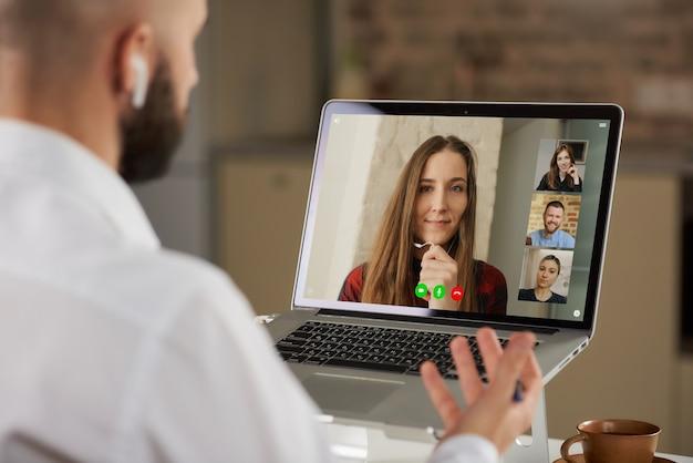 Vista posteriore di un impiegato maschio calvo in auricolari che sta lavorando a distanza gesticolando durante una videoconferenza di lavoro su un computer da casa.