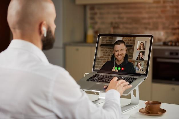Vista posteriore di un impiegato maschio calvo in auricolari che sta lavorando gesticolando in remoto durante una videoconferenza di lavoro su un laptop.