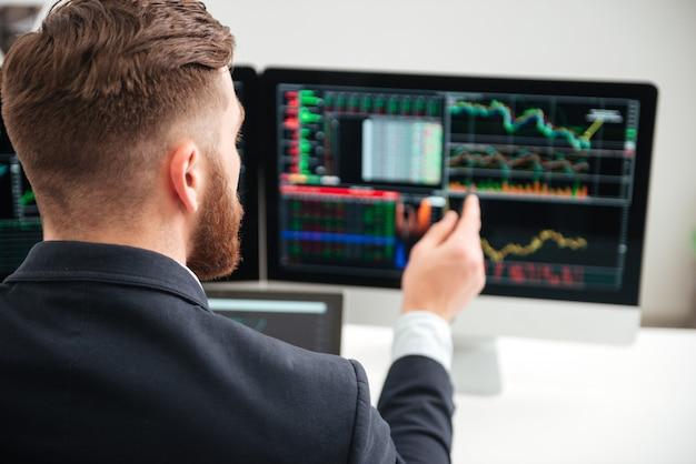 Vista posteriore del giovane uomo d'affari barbuto che si sveglia con grafici e grafici sul computer