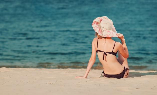 Vista posteriore di una bella giovane donna snella caucasica con un cappello sulla spiaggia, seduta sulla sabbia dorata. ricreazione e coccole in riva al mare (oceano, fiume, lago) in estate e nelle giornate di sole.