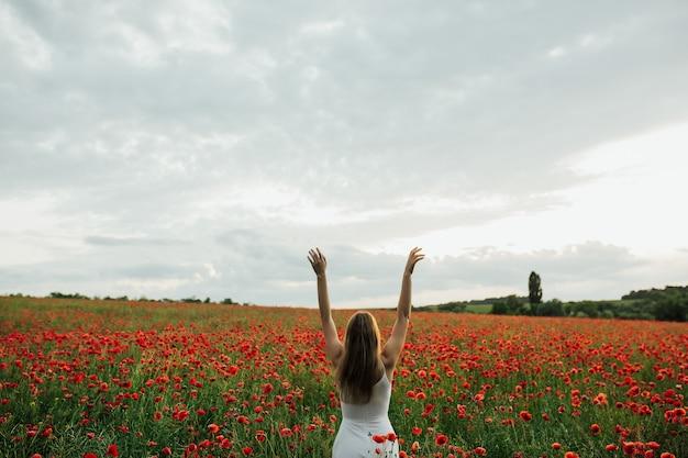 Vista posteriore di una bella ragazza con le mani in alto in un campo di fiori di papavero