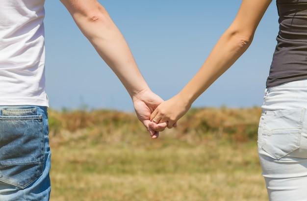 Vista posteriore di una bella coppia d'amore che si tiene per mano all'aperto su uno sfondo di campo estivo summer