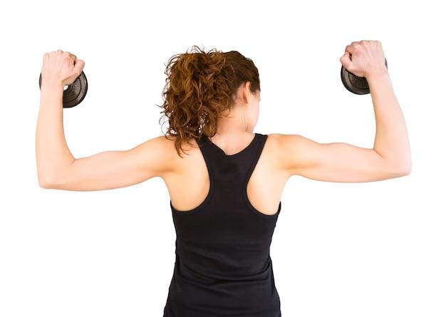 Vista posteriore di una bella ragazza che solleva dischi con manubri in una sessione di allenamento muscolare isolata su sfondo bianco white