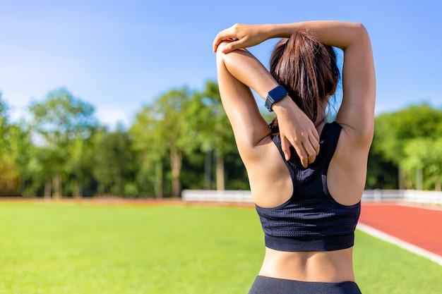 Vista posteriore di una bella giovane donna che si estende durante il suo esercizio al mattino in una pista da corsa