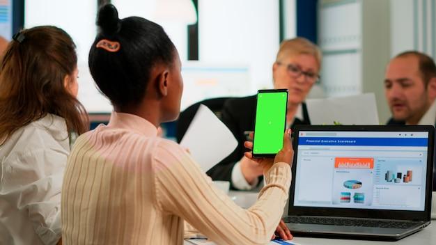 Vista posteriore della donna d'affari nera seduta alla scrivania della conferenza che tiene smartphone con schermo verde mentre i colleghi lavorano sullo sfondo. collaboratori multietnici che pianificano il progetto sul display chroma key