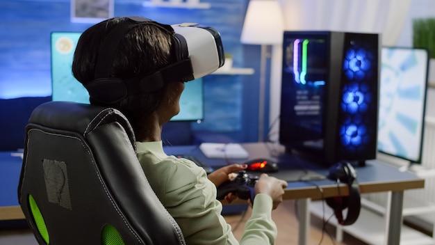 Vista posteriore di una giocatrice di colore che indossa un auricolare per realtà virtuale che gioca con videogiochi sparatutto spaziale con joystick durante un torneo online