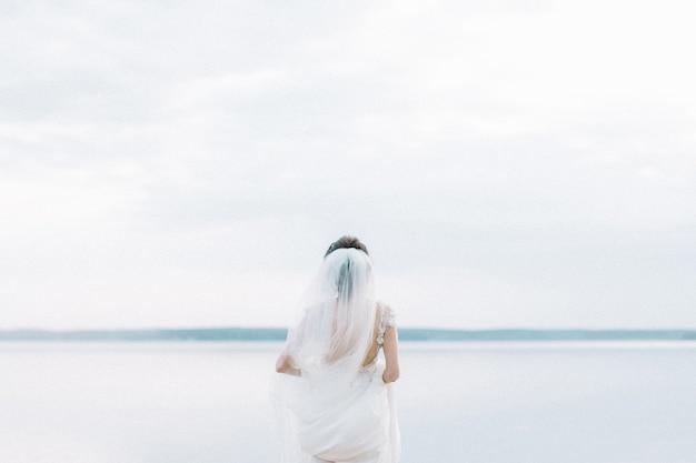 Vista posteriore sulla sposa in abito da sposa guarda l'orizzonte vicino al lago. moda da sposa minimal.