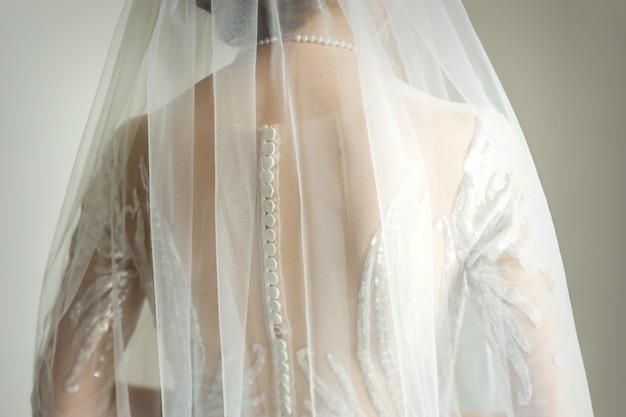 Vista posteriore della sposa in abito da sposa bianco con velo in piedi nella stanza
