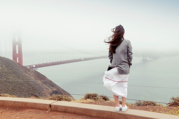 Vista posteriore della ragazza bruna con capelli lunghi in giacca e gonna. la donna si leva in piedi su una collina in tempo ventoso nebbioso