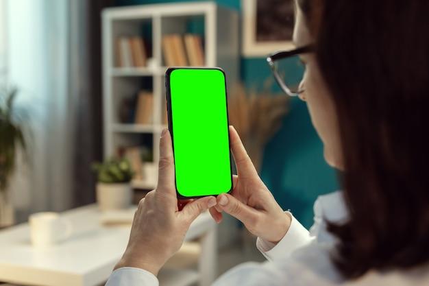 Vista posteriore della bruna con gli occhiali che tiene verticalmente il cellulare con lo schermo verde stare a casa