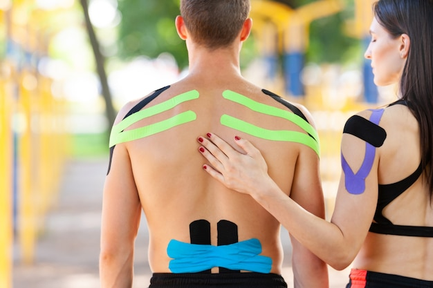 Vista posteriore della donna castana che tiene la mano sulla spalla di un uomo irriconoscibile, atleti caucasici professionisti con nastro kinesiologico colorato sui corpi, in posa al campo sportivo, giorno d'estate.