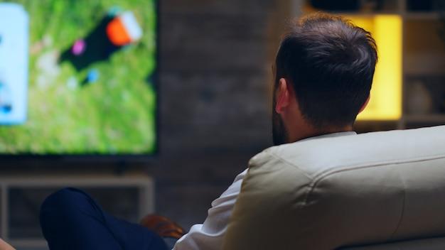 Vista posteriore dell'uomo d'affari che beve un sorso di birra mentre guarda la tv.