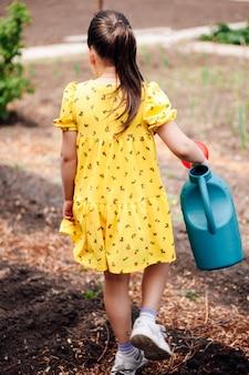 Vista posteriore di una bambina che porta in mano un annaffiatoio da giardino e va ad innaffiare le piante nel...