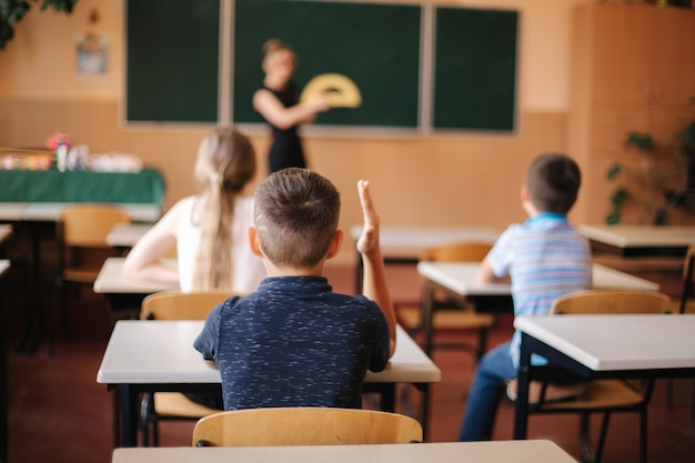 Vista posteriore di bambini seduti in classe e studio. scuola elementare