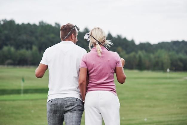 Vista posteriore. coppia di giocatori di golf con bastoni in mano che camminano sul prato.