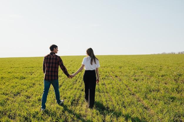 Vista posteriore di una coppia che si tiene per mano e cammina sul campo verde.