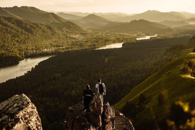 Vista posteriore di coppia uomo e donna in cima alla montagna con zaini al tramonto