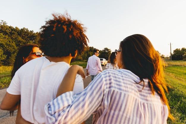Vista posteriore. riccio moro giovane che abbraccia due ragazze. parlano e camminano lungo la strada. .