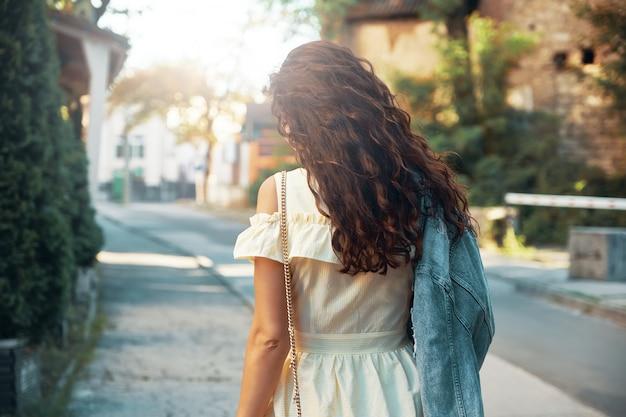 Donna riccia vista posteriore che cammina sulla strada della città
