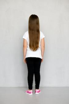 Vista posteriore del bambino in giovane età sveglio con capelli lunghi in maglietta bianca e pantaloni della tuta neri in posa