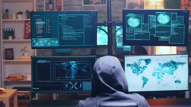 Vista posteriore del cyber terrorista che utilizza il supercomputer per hackerare il firewall del governo.