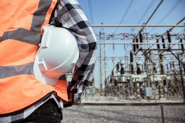 Vista posteriore dell'ingegneria energetica ambientale in piedi e tenendo il casco sul luogo di lavoro