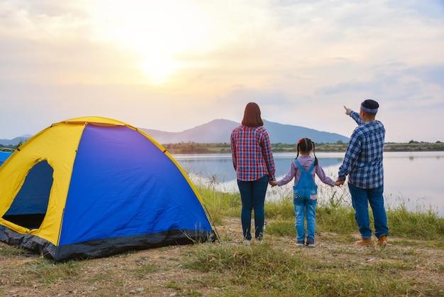 Vista posteriore della famiglia che guarda il tramonto la sera in campeggio in riva al lago