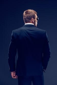 Vista posteriore di un giovane uomo serio con la barba alla moda in abito di lusso con occhiali da sole