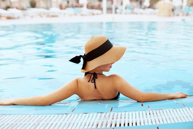 Vista posteriore di una donna alla moda che indossa un cappello e un bikini all'interno di una piscina