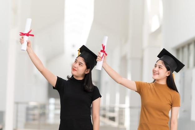Vista posteriore di studenti universitari femminili laureati in possesso di diploma