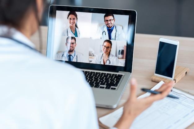 Vista posteriore della dottoressa che parla con i colleghi tramite una videochiamata con un laptop durante la consultazione.